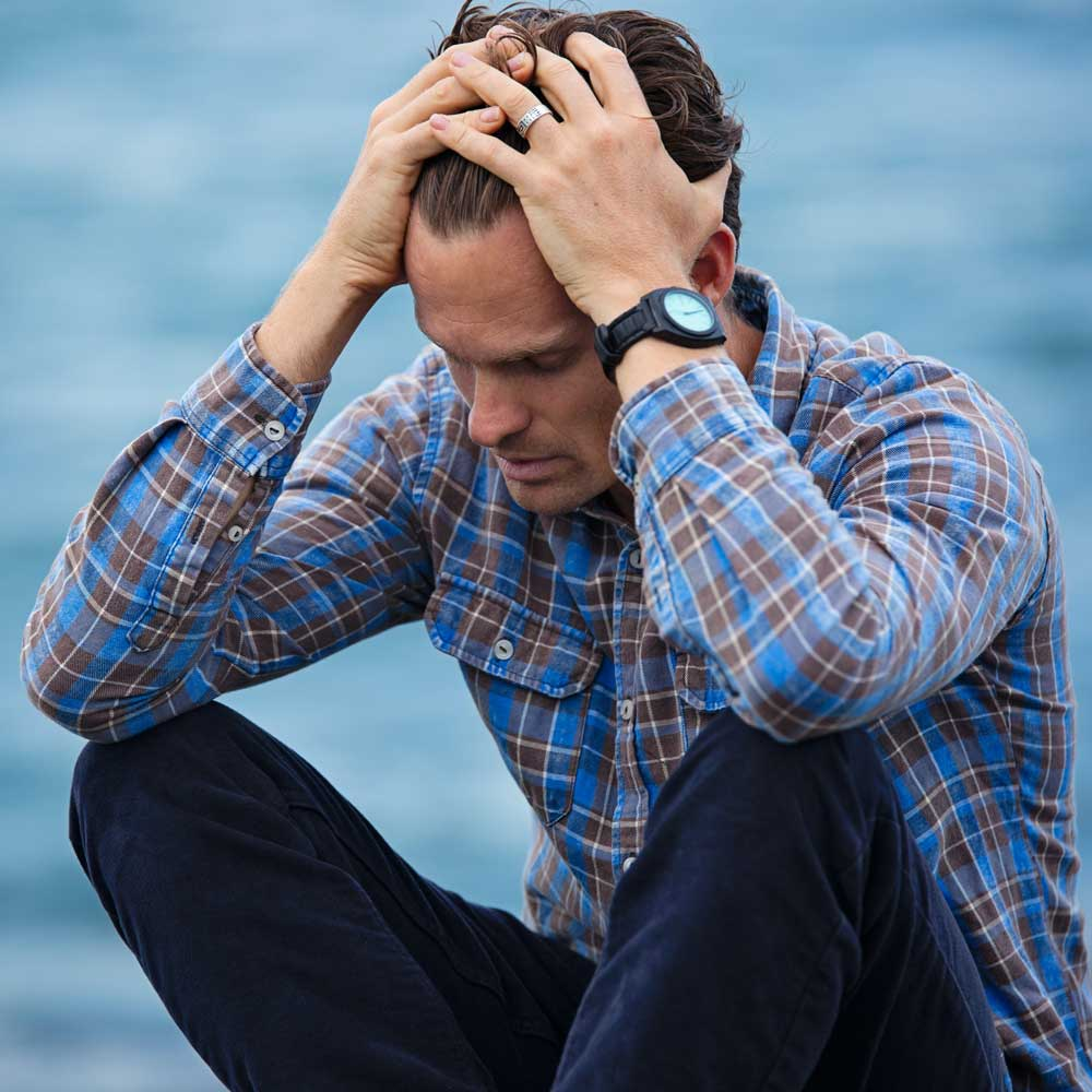 Man in blue plaid with hands in hair, frustrated